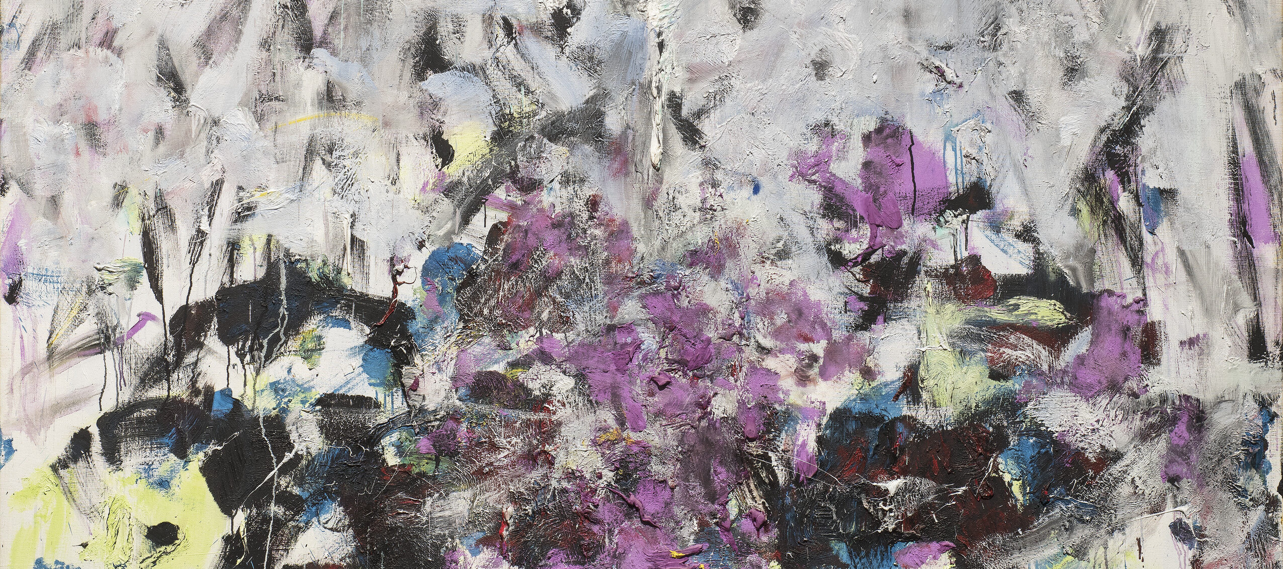 A vertical, abstraction features broadly painted strokes of pale gray, lavender, and cobalt in the upper two-thirds of the canvas. The colors continue in the lower third, along with touches of green, black, and other hues, but the expressive brushwork becomes denser and chaotic.