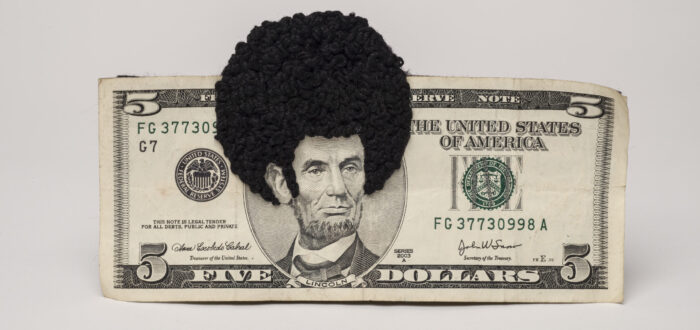 U.S. five-dollar bill has an embroidered afro and sideburns stitched onto the portrait of Lincoln's head. One-third of the afro protrudes beyond the top of the bill.