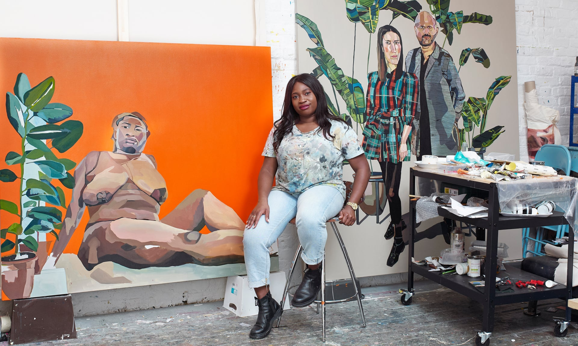 A dark-skinned woman sits on a stoll in an art studio in front of two large portrait paintings. Next to her is a cart filled with painting supplies.