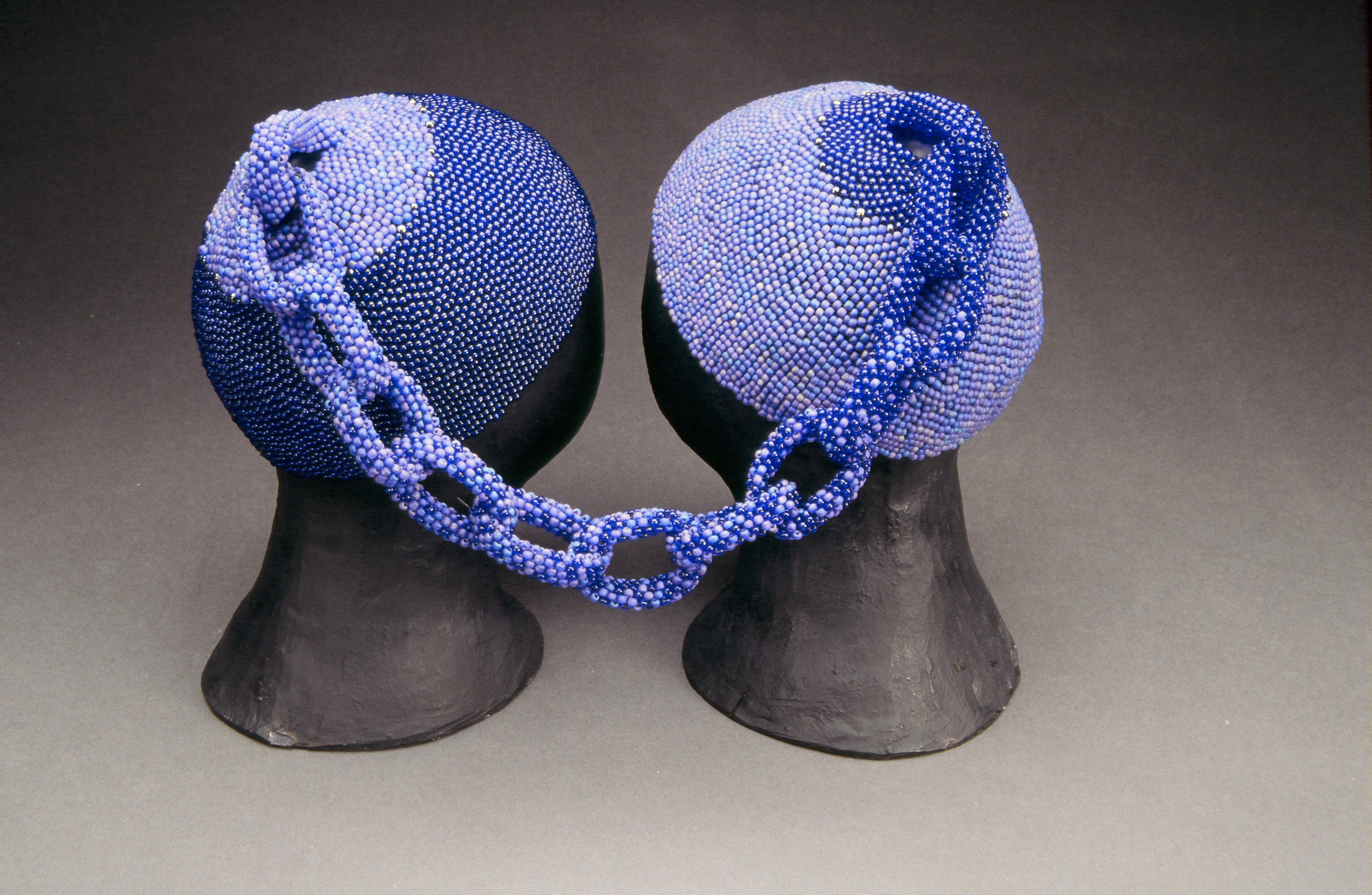 Two head caps made of small, blue glass beads rest on two black mannequin heads. The two caps are connected at the tops by a beaded chain. The left cap is made of darker blue beads and the right cap is made of lighter blue beads. The chain combines both shades.