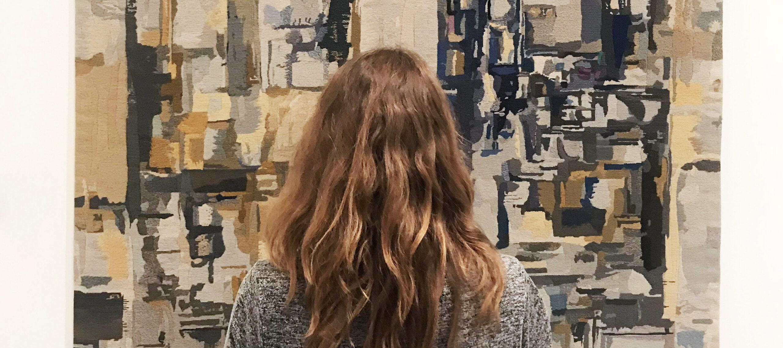 A light-skinned adult woman in a gray dress with medium-length, wavy, brown hair is seen from behind, standing and facing a large, abstract painting. The painting depicts blurry, layered rectangles and squares in shades of gray, taupe, and black, layered and appearing to recede.
