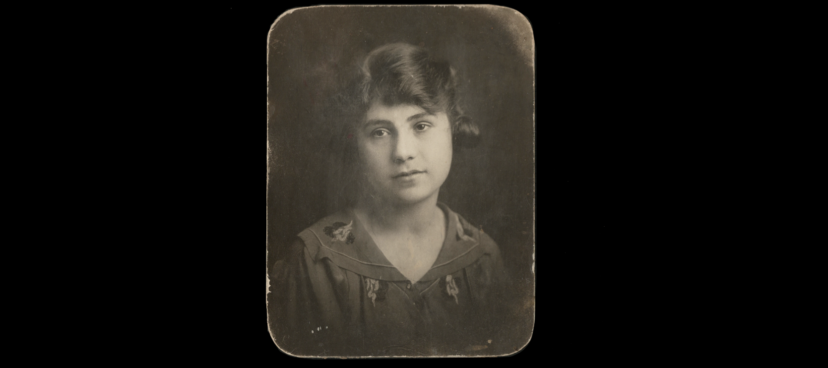An antique sepia photo portrait of a light-skinned woman with brown hair staring longingly at the camera.