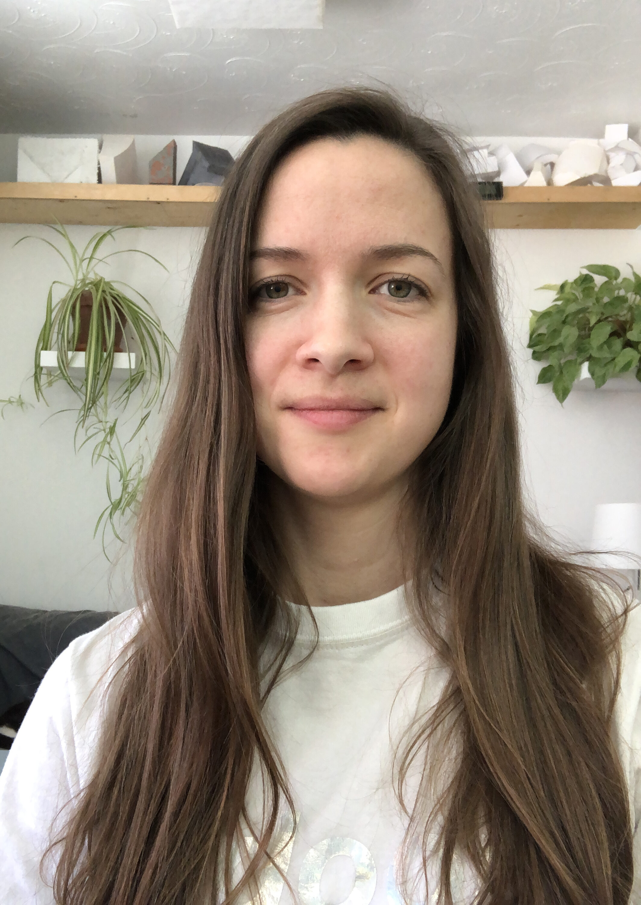 A light-skinned woman with long straight brown hair smiles at the camera. In the background two lush plants are on shelves. The rest of the room is white.