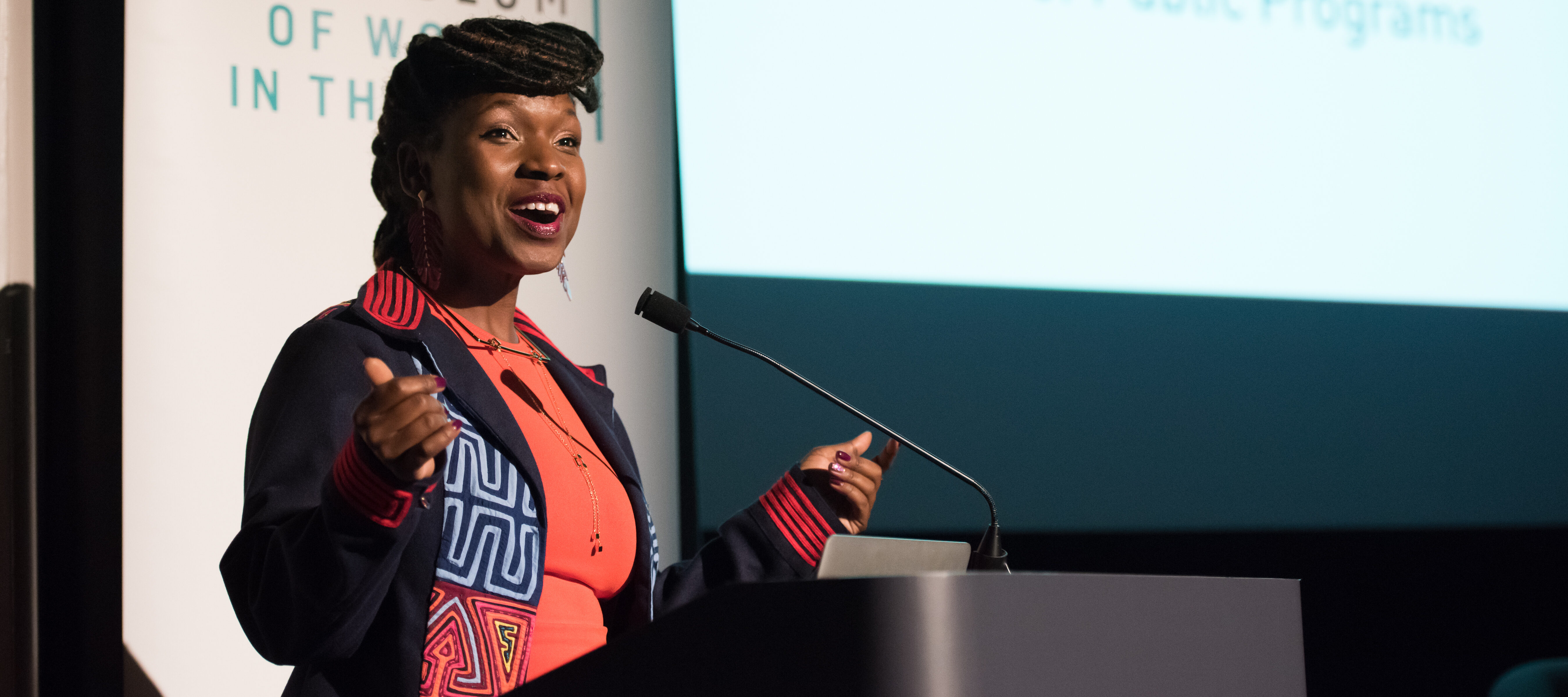 Melani N. Douglass speaks at a podium at the National Museum of Women in the Arts during a Fresh Talk event. She is a dark-skinned adult woman wearing a colorful top and smiling.
