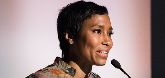 "A dark-skinned woman with short cropped hair speaks into a microphone at a podium. Behind her a banner reads ""National Museum of Women in the Arts."" She wears a colorful abstract print blouse."