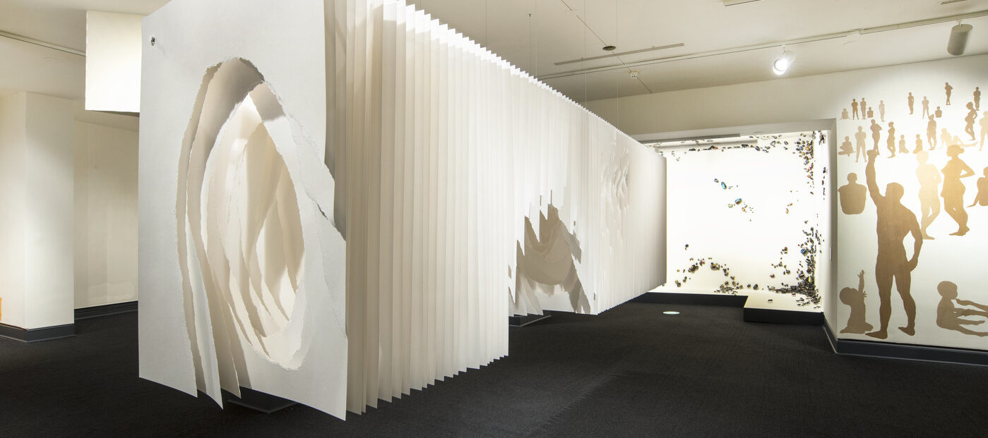 Panels of white paper hung together to look like a long rectangular box suspended from the ceiling a few feet off the ground. Roughly torn holes in the middle of the sheets create a tunnel-like space.