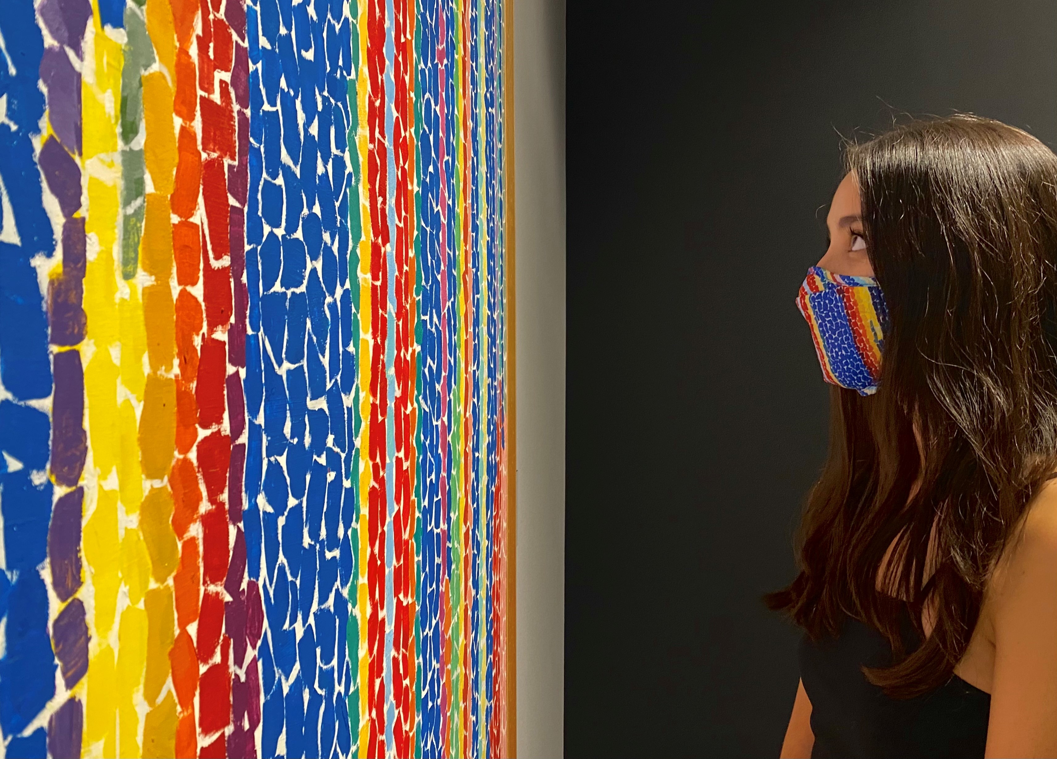 A young woman with long brown hair stands in front of a painting by Alma Thomas with long vertical bands of rainbow colored brush strokes. The woman is wearing a face mask that matches the painting.