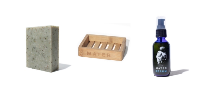 Three Mater Soap products against a white background. On the left is a green, flecked bar of soap. A wooden, slatted soap dish with MATER on the side is in the center. On the right is a small blue pump bottle with the Mater Serum label on it.
