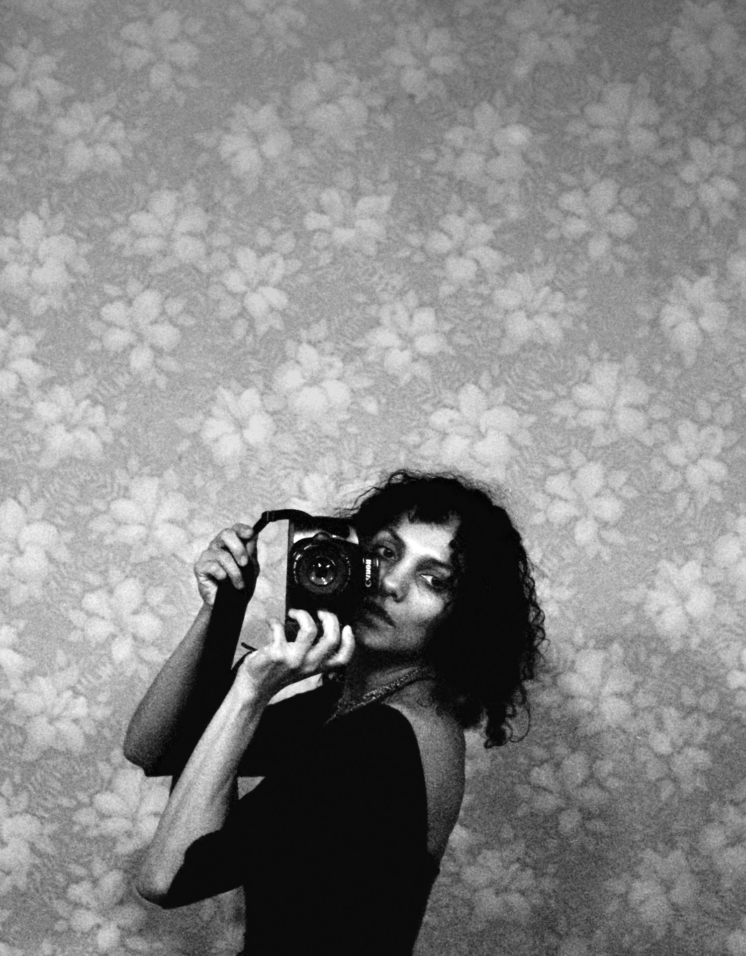 A black-and-white self portrait of a woman standing in front of patterned floral wallpaper. She stands to the side and turns her head forward, holding a camera up. She is visible from the waist up and wears a black leotard.
