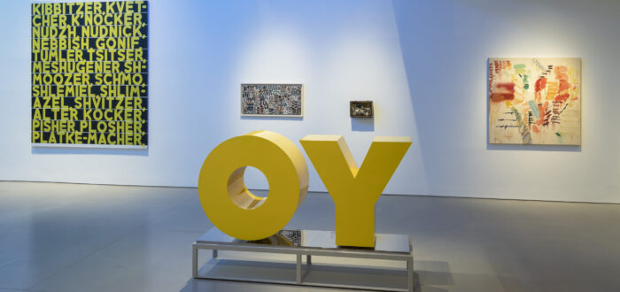 """In a museum gallery space, a large yellow sculpture of the word """"OY"""" is in the center of the room with four paintings of large and small sizes behind it. The white wall is awash in blue light."""