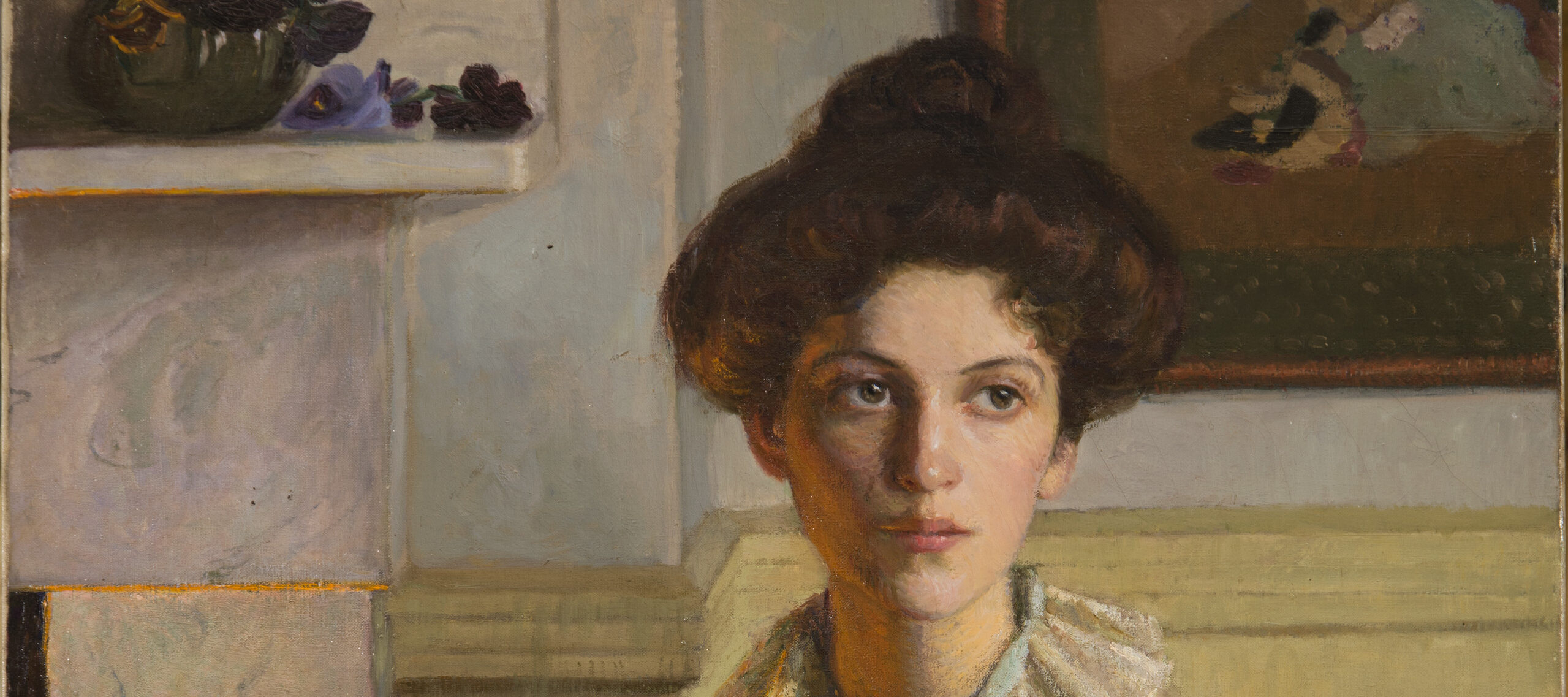 A young woman sits on a chair with her hair in a loose bun, wearing a white lace-trim gown. Her body turns slightly right towards a fireplace, its orange glow reflected on her hair and torso. The room is light and clean and a dark bowl overflowing with violets sits on the mantle.