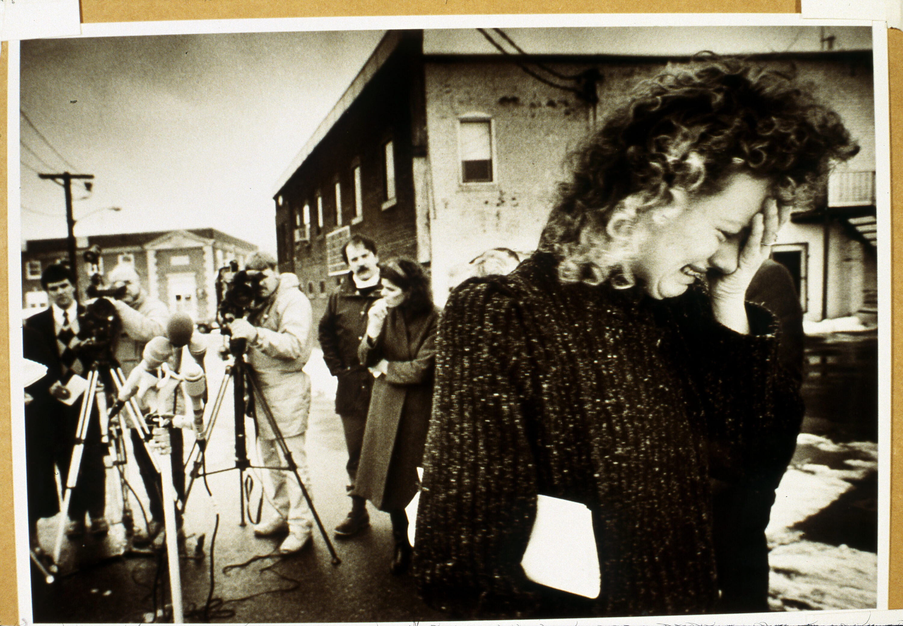 A black-and-white photograph of a light-skinned adult with curly hair crying into their hand. They wear a sweater and stand in the foreground, seen waist up, while several photographers swarm in the background behind a microphone stand set up in the middle of the street.