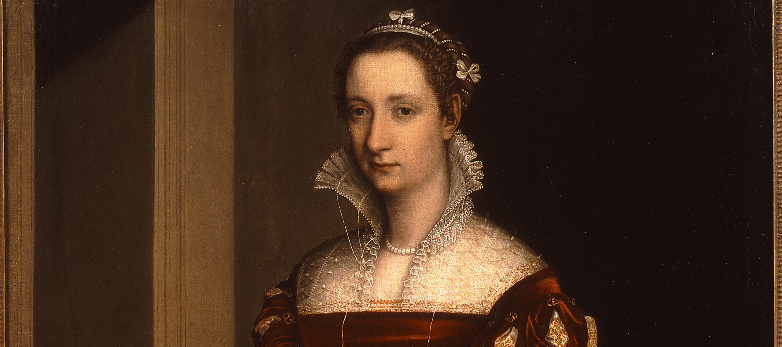 Three quarter length painting of a woman standing against a dark background. She is wearing a sumptuous red Renaissance-style dress with a high lace collar. Standing next to her at bottom left is a child holding a small spaniel.