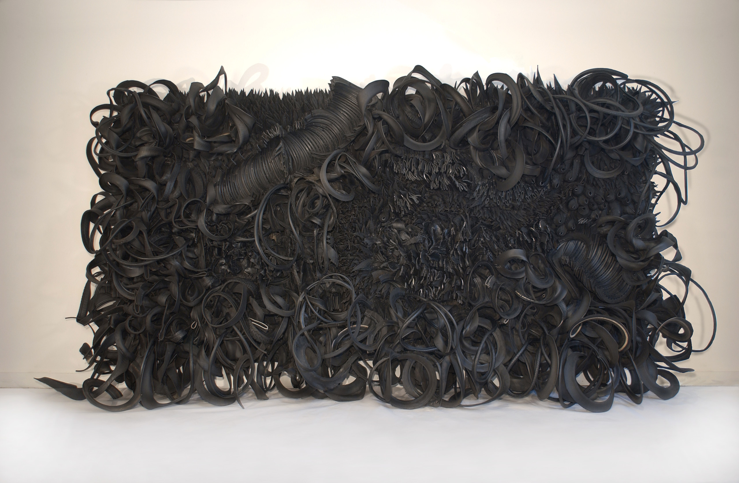 The wall-sized, horizontal sculpture consists of black rubber tires and tubing that has been sliced, stripped, woven, looped, twisted and otherwise manipulated into an expressive and abstract high-relief tableau.