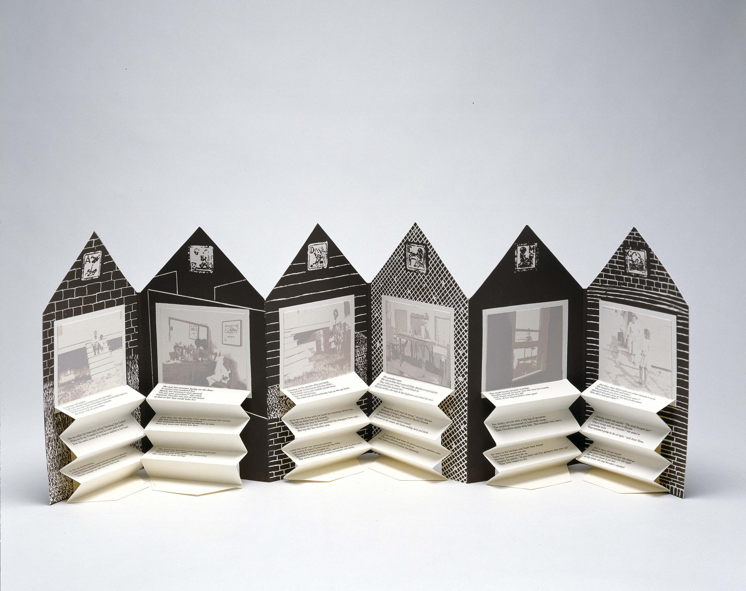 An open accordion-style book in the shape of a house. On each page is a black and white graphic background and a washed-out black and white photograph. Beneath each image is typed text on accordion folded paper.