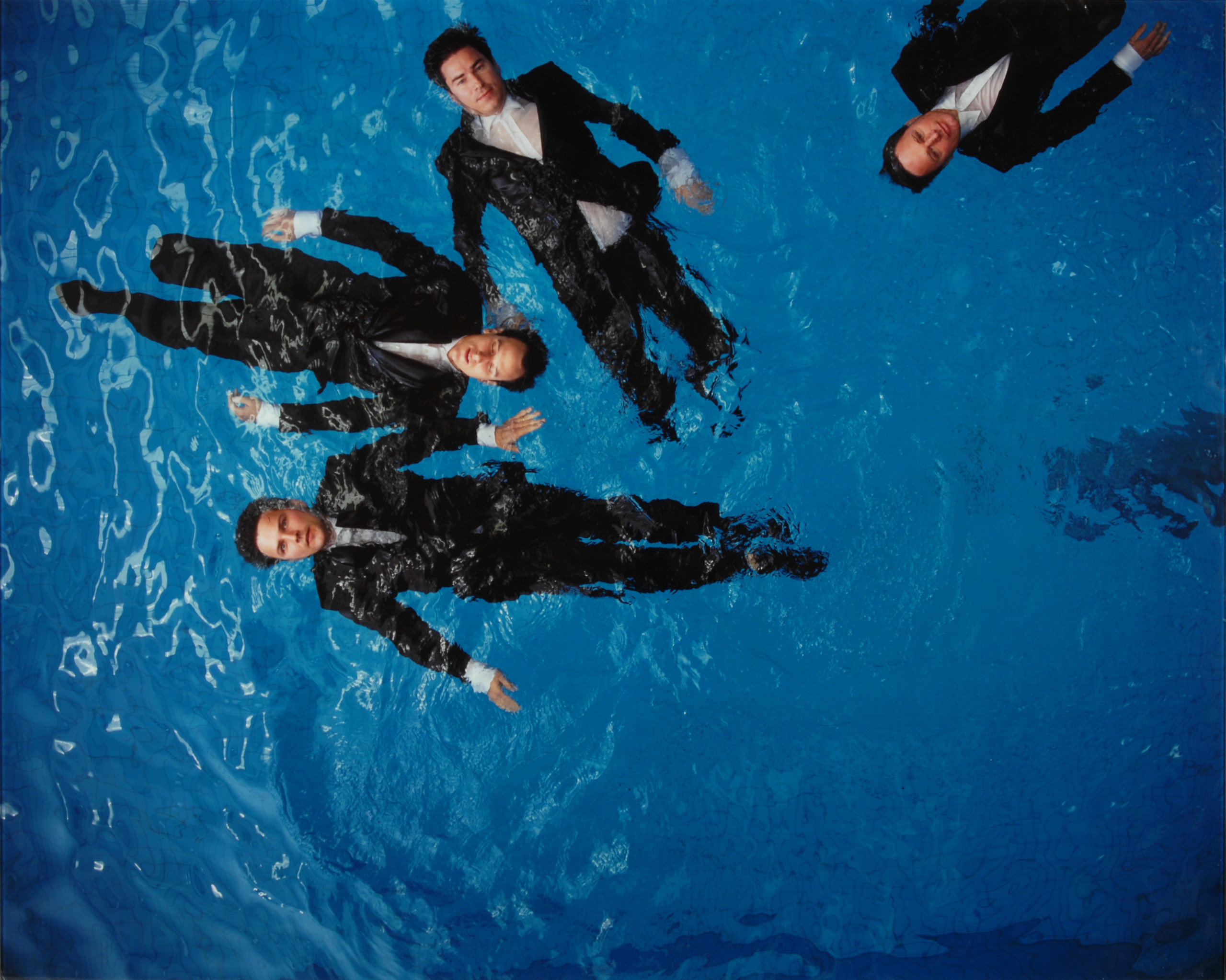 A photograph of four light-skinned figures with short brown hair, wearing black suits with white shirts, floating on their backs in a deep blue pool. The viewer looks down on the figures from above. One figure has their eyes closed, the rest have their eyes open.