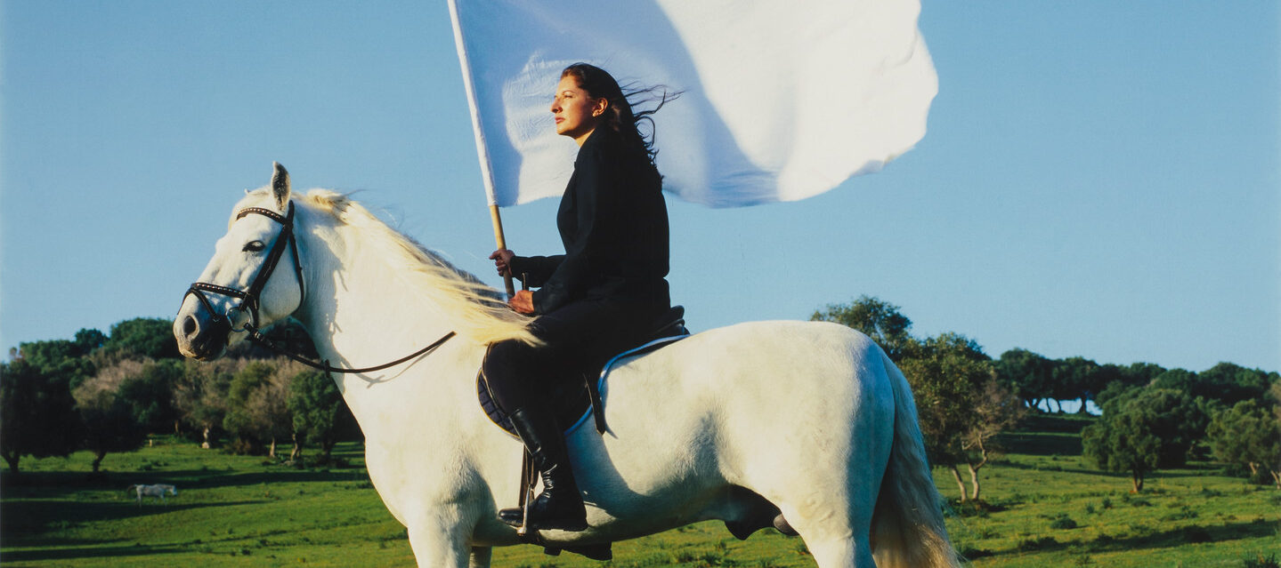 Color photograph of a light skin toned woman in all black on a white horse and carrying a large, white flag. Horse and rider are facing left and are in a rolling green landscape with a bright blue cloudless sky.