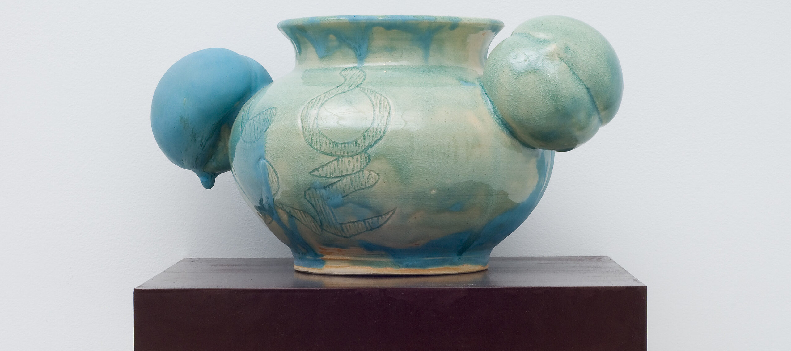 A round, ceramic vessel glazed unevenly in glossy celadon has a bulging body incised with abstract shapes. Matte turquoise glaze dribbling down from the rim obscures portions of the pale green and fully coats one of two peach-shaped orbs projecting from either side of the neck.