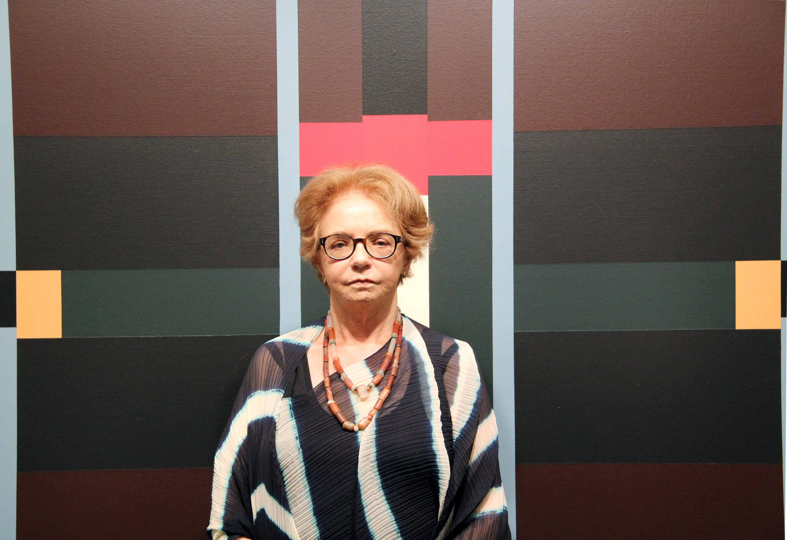 A light-skinned older woman with short, light brown hair stands in front of an abstract painting. She wears glasses, a black and white striped shirt, and two beaded necklaces. The painting behind her depicts black and maroon planes atop which red, teal, peach, and light blue lines and rectangles are rendered.