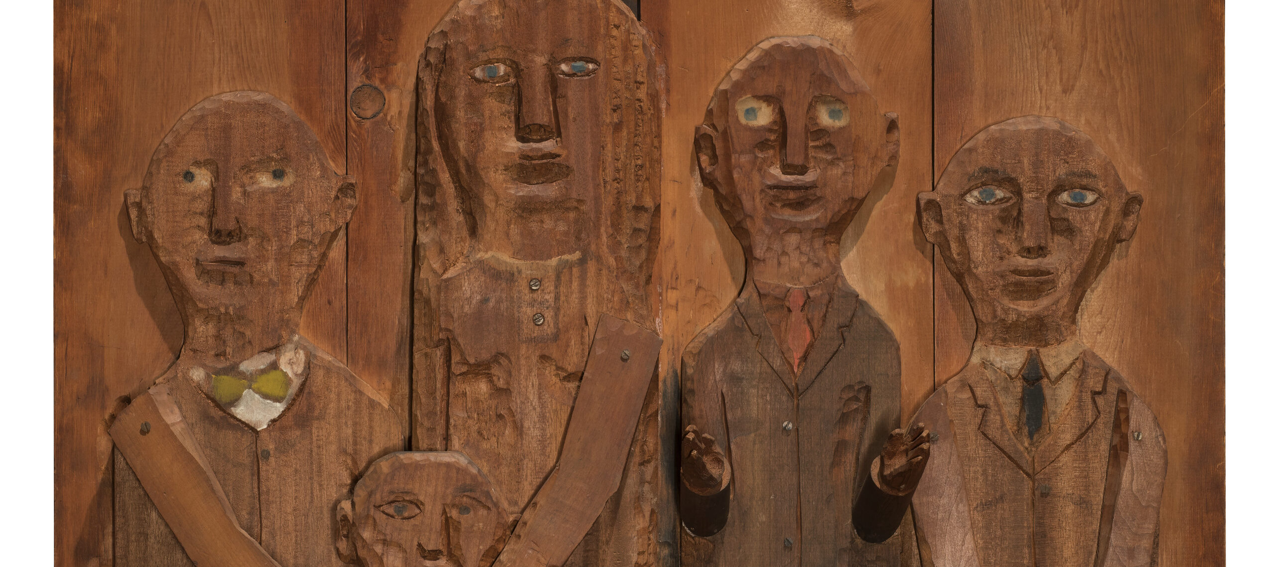 A wooden relief sculpture of four adults and one child. The two figures on the left put their hands on the shoulders of the child in front of them. The arms and hands of all figures are three dimensional and protude from the work.