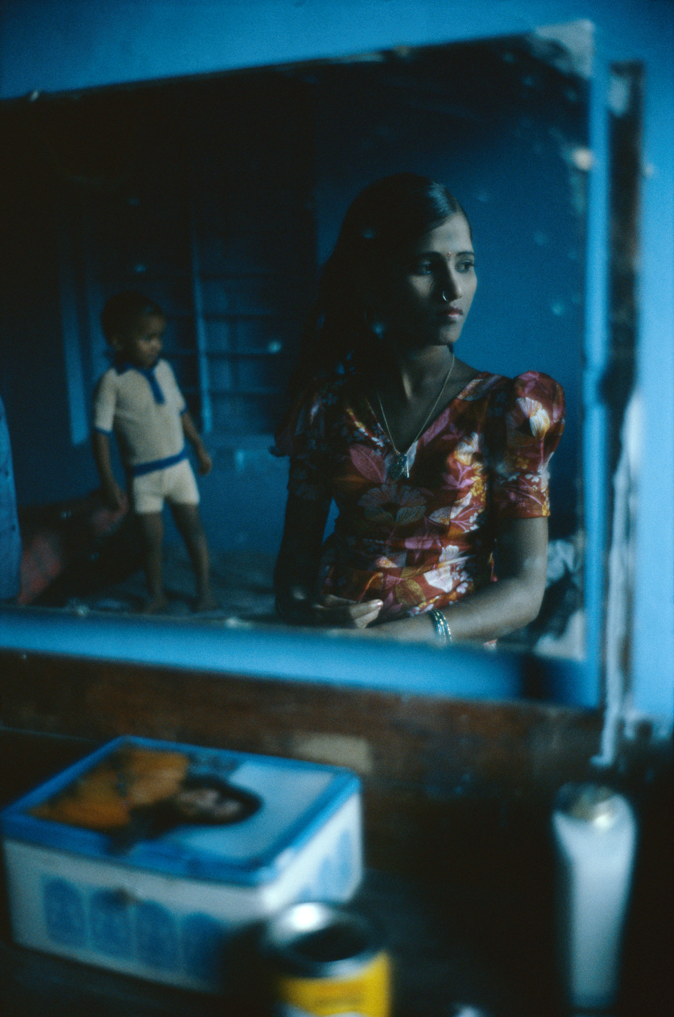 A dresser mirror reflecting a medium dark-skinned woman with long, dark hair in a vibrant red, yellow, and white dress. She faces slightly right, half of her in shadow, and wears a bindi and nose ring. Behind her is a medium-dark skinned child and they are in a very blue room.