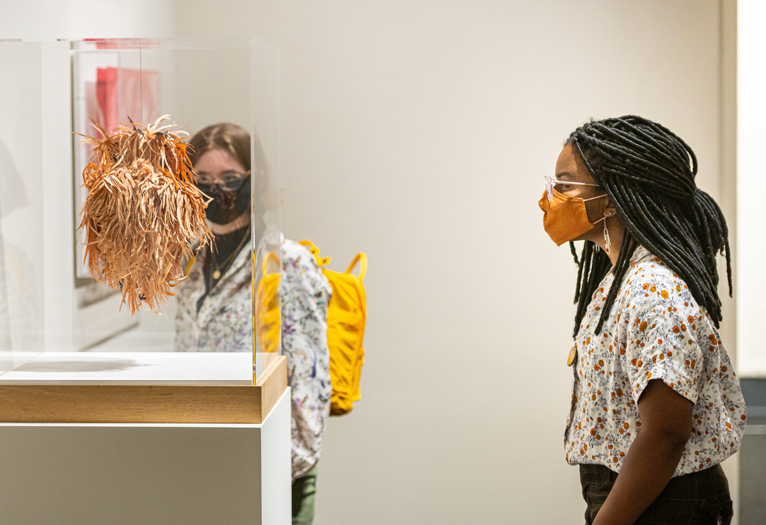 Young woman with long, thin braids, wearing glasses and an orange face mask, looks at a small hanging sculpture made of thinly cut strips of pale orange paper.