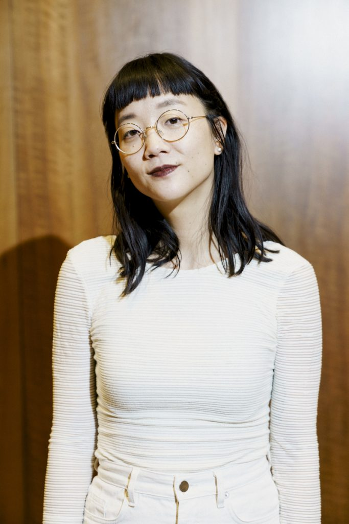 A casual portrait photograph of a light-skinned Asian woman wearing a tight white long sleeved shirt and white jeans. She smiles slightly at the camera. She wears her black hair down at shoulder-length and circular, thin-rimmed classes.
