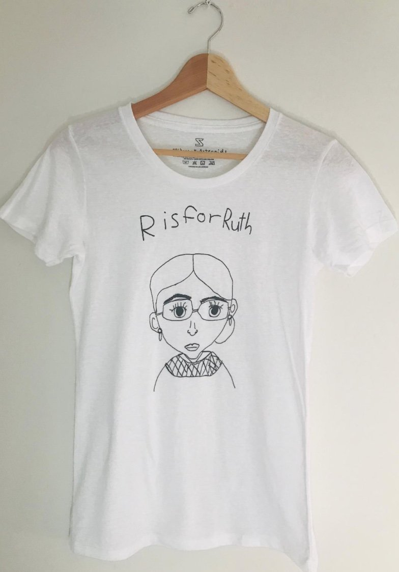 "A white t-shirt with a simple pencil drawing of Ruth Bader Ginsburg's likeness. Above it, written in children's handwriting is the phrase ""R is for Ruth."""
