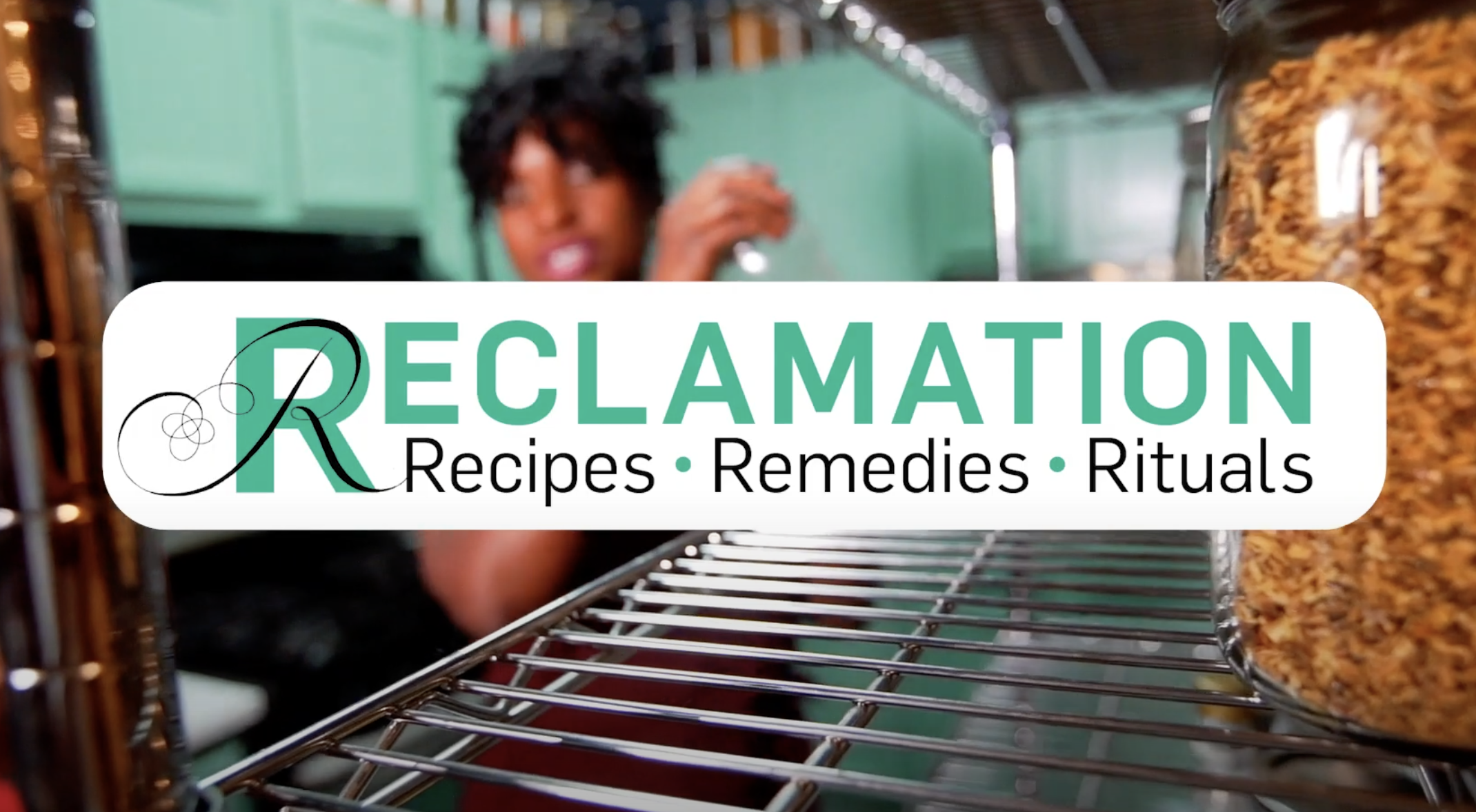 A white rectangle with green and black text that reads 'RECLAMATION: Recipes, Remedies, Rituals'. Behind the rectangle is a blurry image of a dark-skinned adult woman and her dark-skinned child in a turquoise-colored pantry, with a metal rack and a jar in the foreground to the right.