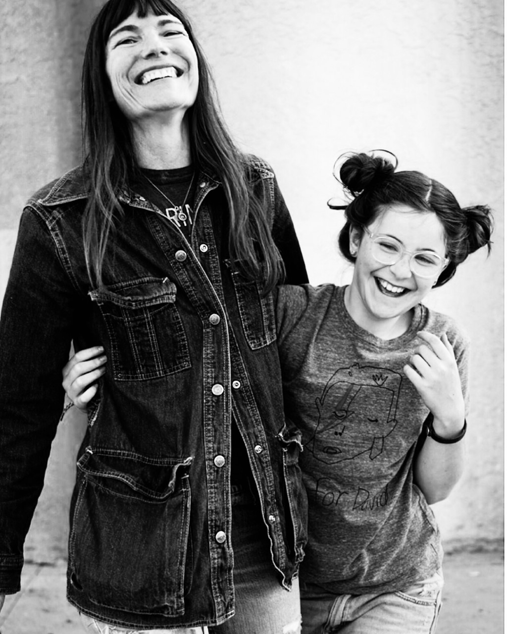 A black-and-white photo of a light-skinned mother and daughter, who have their arms around one another and are laughing joyfully.