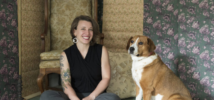 A light-skinned woman with shoulder-length brown hair smiles at the camera. She wears octagonal earrings and a sleeveless black shirt that reveals one arm full of flower tattoos. Sitting next to her is a brown and white dog, looking off into the distance. They are both positioned in front of floral patterned wallpaper and an antique chair, also covered in a floral pattern.