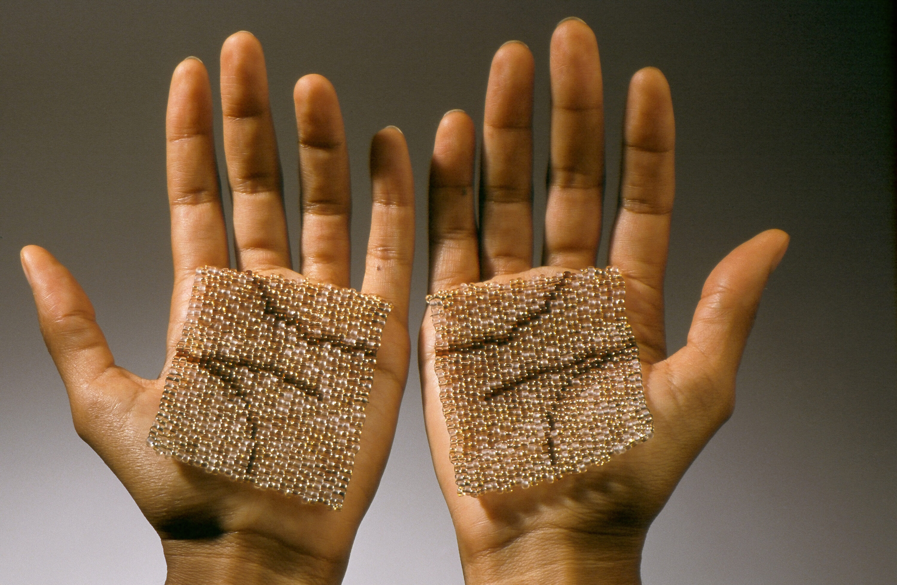 A pair of medium-dark skinned hands held up next to each other, palms up. Resting on each palm is a square made of glass beads in colors matching the skin. Dark brown lines on the squares map directly over the natural palm creases of the hands.