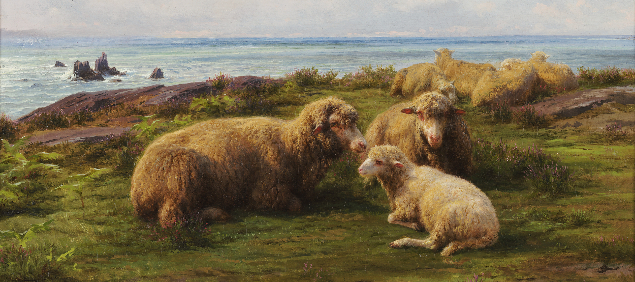 A flock of sheep rest on a green hill by the sea. In the center, two adults and a lamb lie in a group. Flat rocks are visible through the grass. The sky has rolling clouds, and a breeze is suggested by the waves crashing on rocks in the sea, which stretches to the horizon.