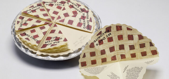 A pie tin filled with eight small folded pieces of paper that resemble identical slices of pie with a lattice top and red filling. Each slice is labeled with a title in black and opens, containing short stories written inside.