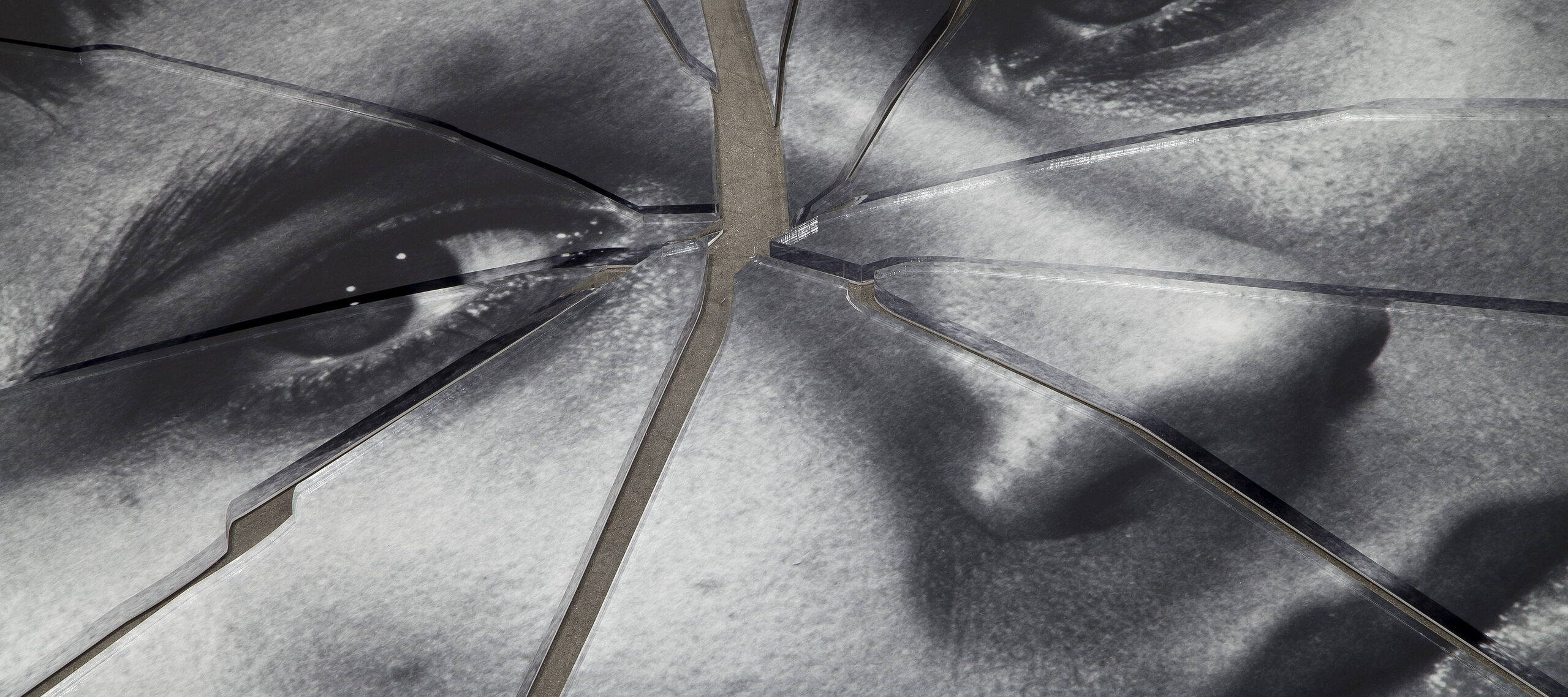 A detail shot of a black-and-white image of a person's face printed on plexiglas that has been shattered in the center.
