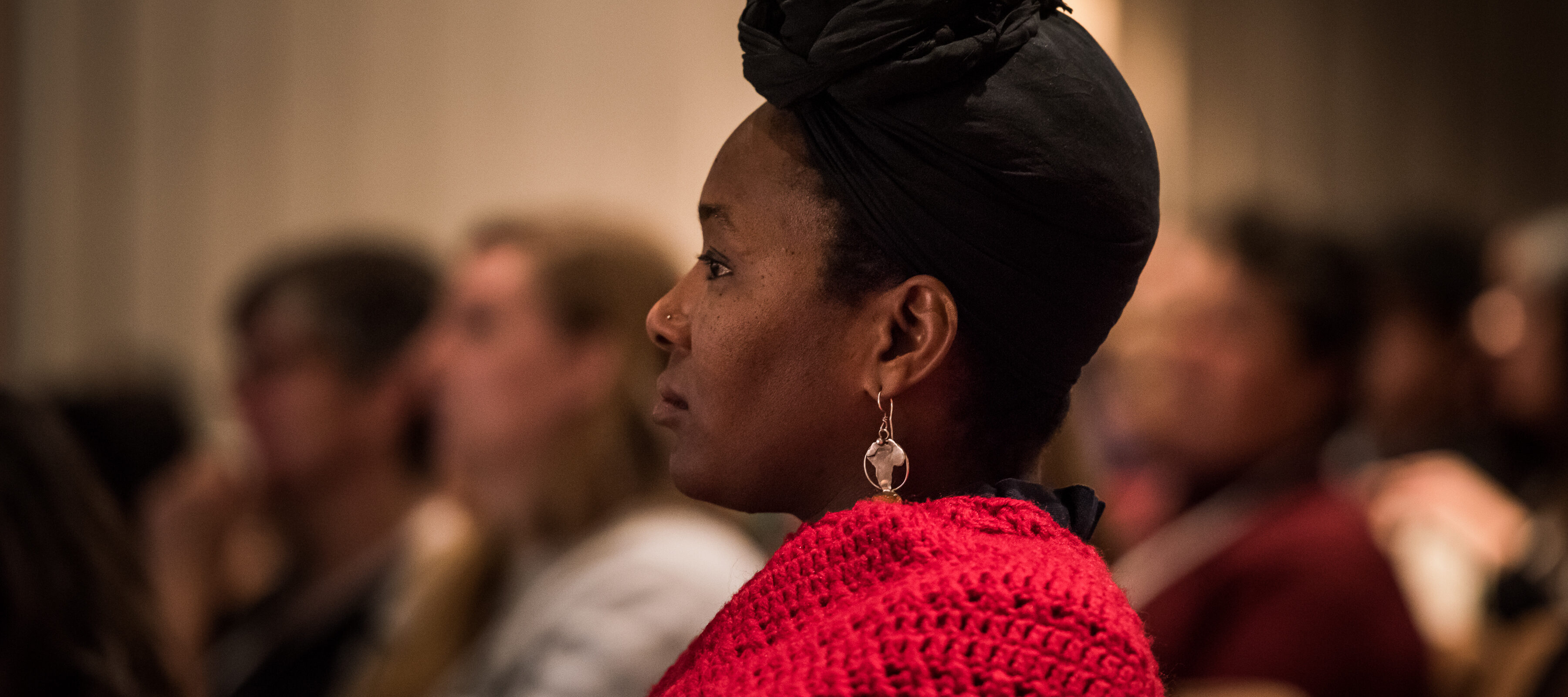 A dark-skinned adult sitting in profile, seen from the shoulders up. They wear a red sweater, gold earrings, and their hair tied up in a black headscarf. They sit in an auditorium, with blurry figures filling the seats in the background.
