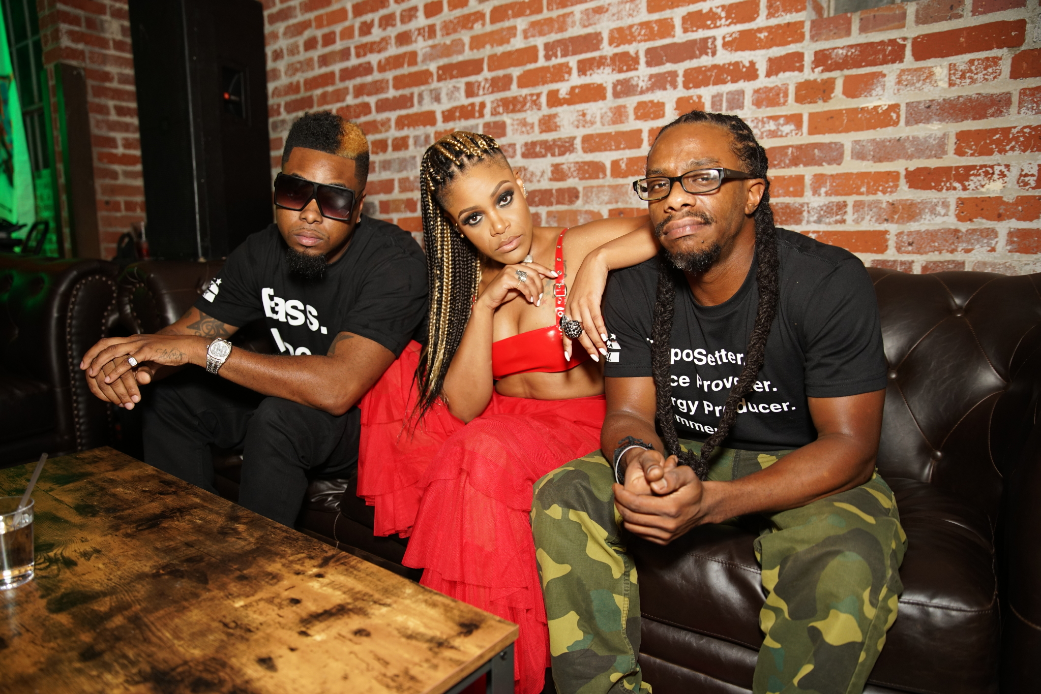 Three adults sit on a black leather couch together in a red-brick room. In the center is a medium skinned woman with long braids wearing a red outfit, and to her left and right are dark-skinned men wearing glasses and black t-shirts.