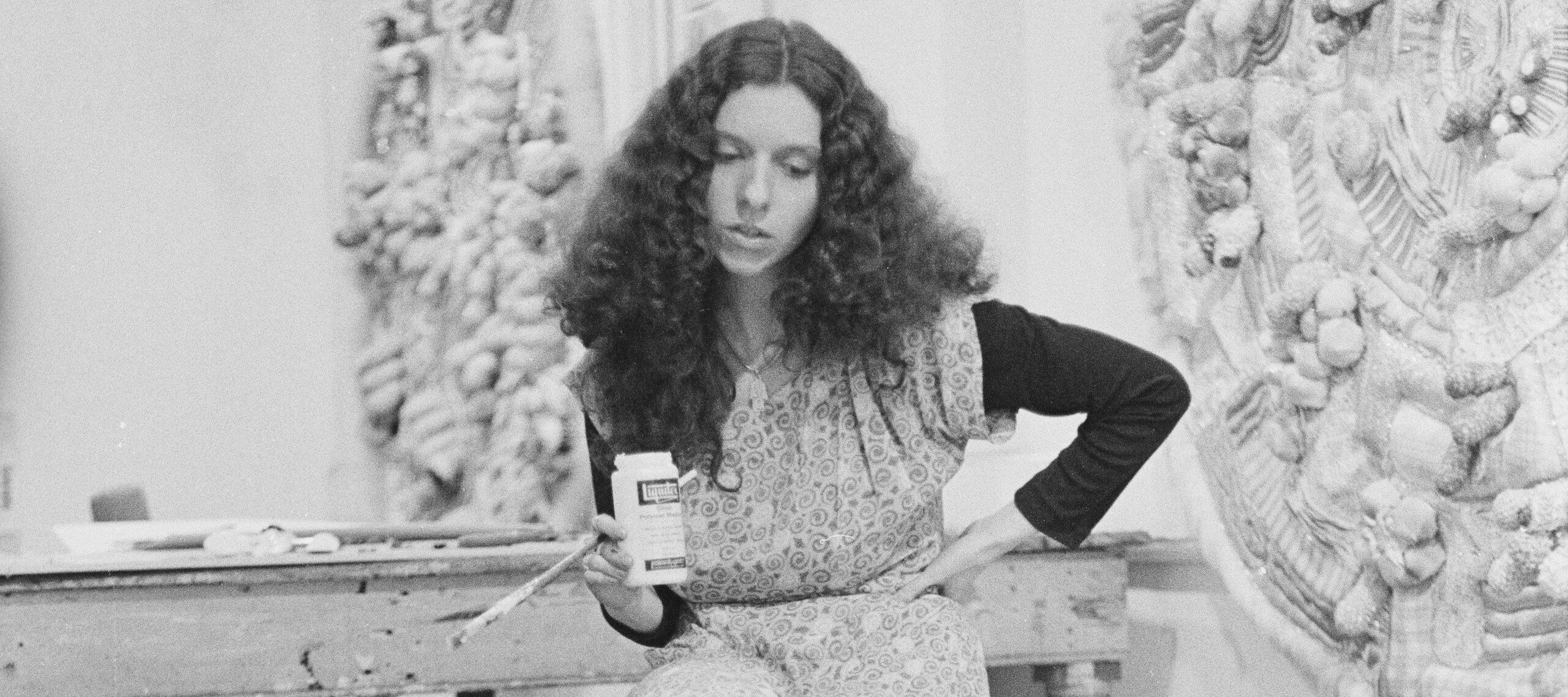 A black-and-white photo of a light-skinned woman sitting on a stool in an artist's studio, looking down at a large circular fabric/textile work. She holds a bottle of gesso and a paint brush.