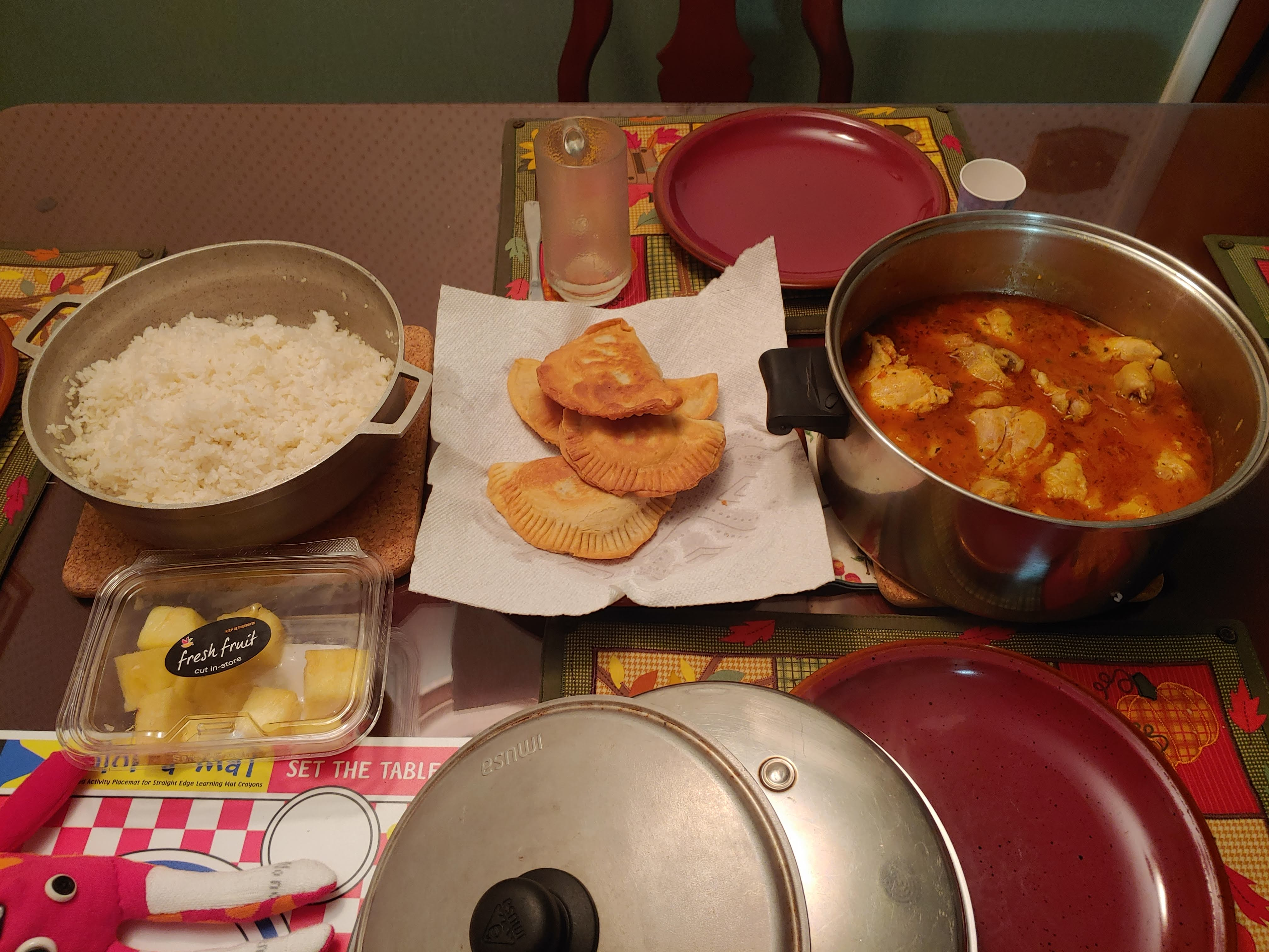 An overhead photo of a dining table that holds one large pot of white rice, four fried beef/flour patties atop a paper towel, a stainless steel pot of chicken in a red sauce, and a plastic container of pineapple. Dark red ceramic plates sit atop a fall/harvest scene on cloth placemats.