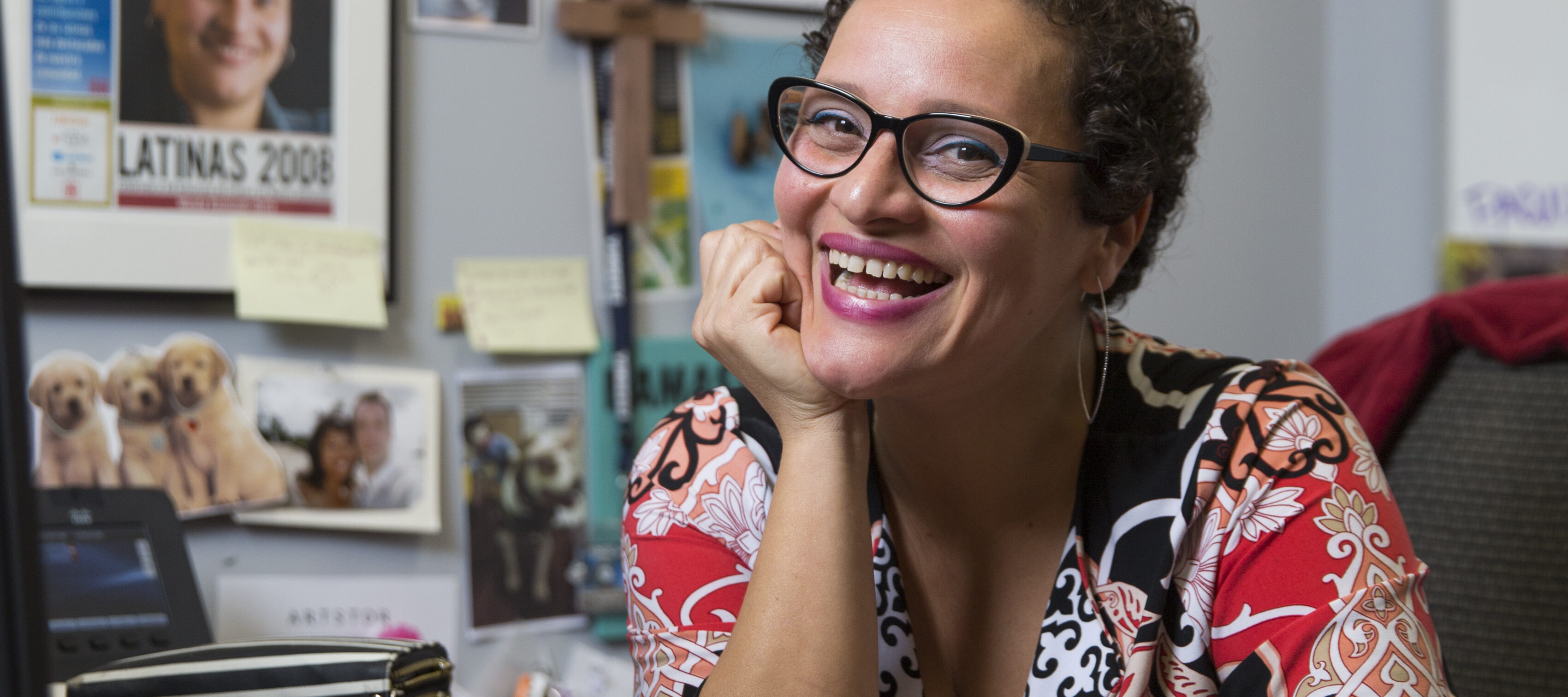 A olive-skinned woman smiles brightly, seemingly mid-laugh, as she sits at an office desk, her right hand placed beneath her chin. Her brown curly hair is worn in a cropped pixie cut and she wears cat-eye glasses. In front of her is a closed Apple laptop; the wall behind her holds two framed certificates or degrees, a framed newspaper, a wooden cross, and other pasted photos.