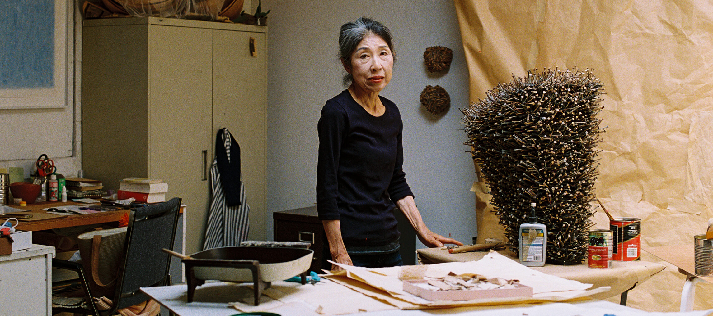 In a white brick artist's studio, a small light-skinned Japanese woman stands amongst various supplies, including work paper, paper sculptures, scissors, glue sticks, and paint cans. She wears a black shirt and stares directly at the camera, unsmiling. Her black hair is pulled back and she has streaks of white hair at her hairline's part.