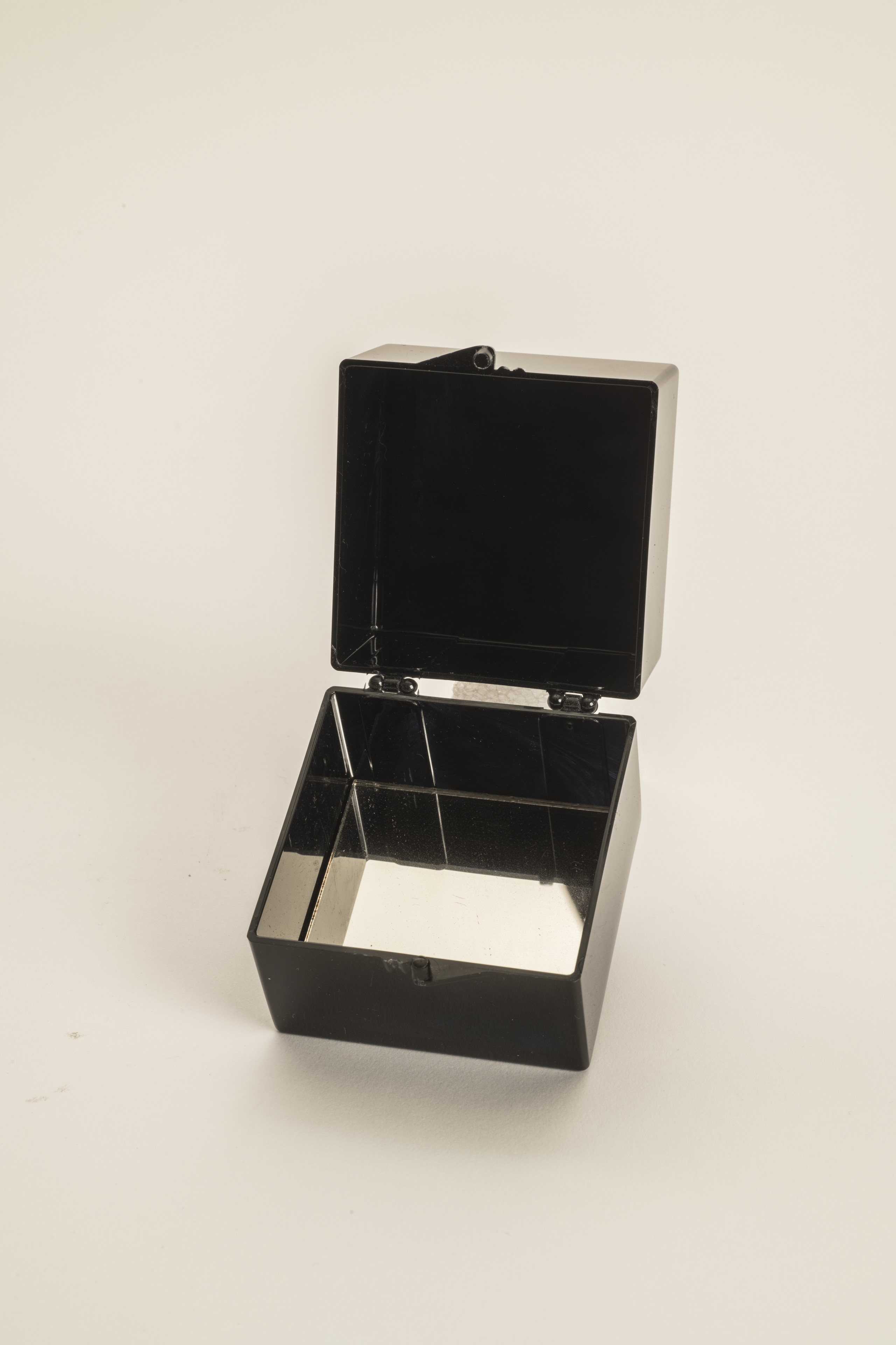 A small black plastic box that is opened to reveal a mirrored interior bottom.