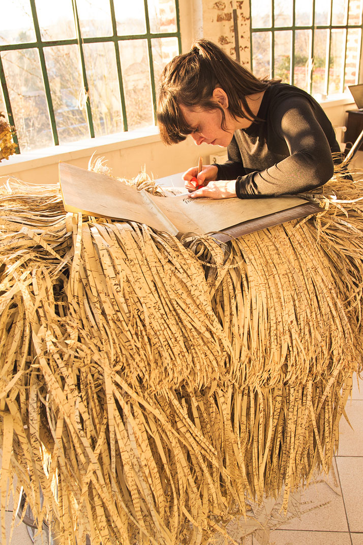 A light-skinned woman with straight brown hair worn in a ponytail and long bangs is at a desk hunched over a book or pieces of paper, which sits atop a huge pile of long, cut strips of paper that layer to resemble feathers.
