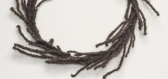 A circular wreath made of dark, tightly coiled hair with strands escaping and resembling laurels.