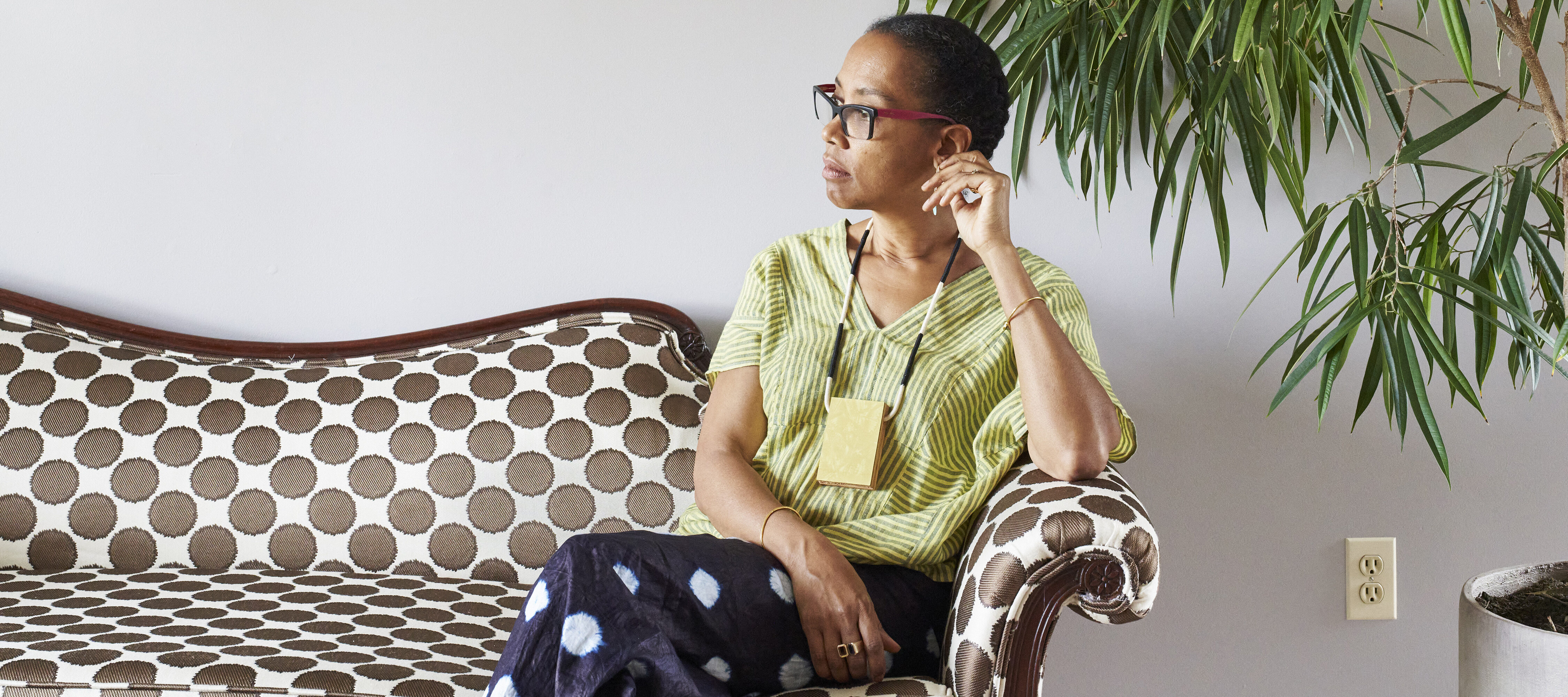 Sonya Clark calmly sits on a polka-dot couch against a white wall, next to a large plant. She is a medium-skinned adult woman with dark hair pulled back, looking to her right with her legs crossed. She wears a striped top, black pants with large white dots, glasses, and a necklace.