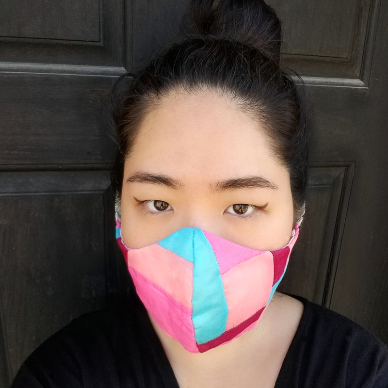 A light-skinned Asian woman wears a colorful patchwork face mask.