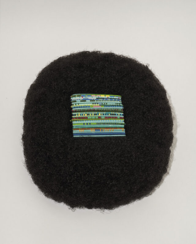A square of bright, multicolored threads of blue and green tones rest in the center of a circular afro wig made of black hair.