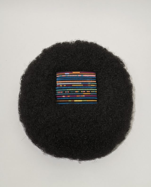 A square of bright, multicolored threads rest in the center of a circular afro wig made of black hair.