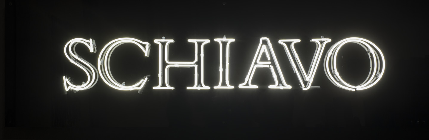 """White neon letters against a black background. The letters light up to read """"schiavo."""""""