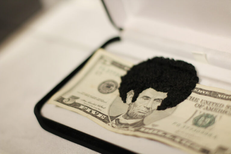 An American five-dollar bill that has been embroidered with black thread to give the portrait of Abraham Lincoln a large Afro and sideburns, which protrudes beyond the top of the bill.